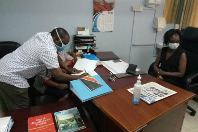 UHS Bursar Mr. Otiende signing and Looking on is outgoing CMO Dr. Asimba
