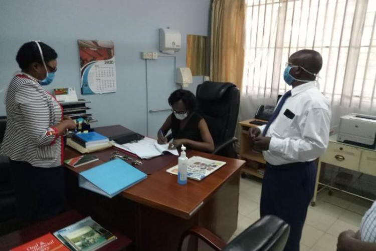 Former CMO Dr. Asimba signing handover notes  witnessed by Incoming CMO  Dr. Muhia and UHS Admin Mr. Kinyanki